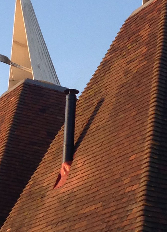 Flue installation in oast house roof
